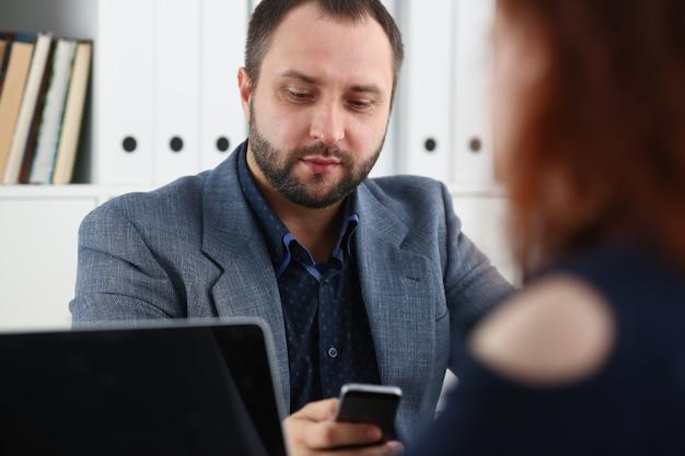 Zakenman op een vergadering met behulp van zijn smartphone