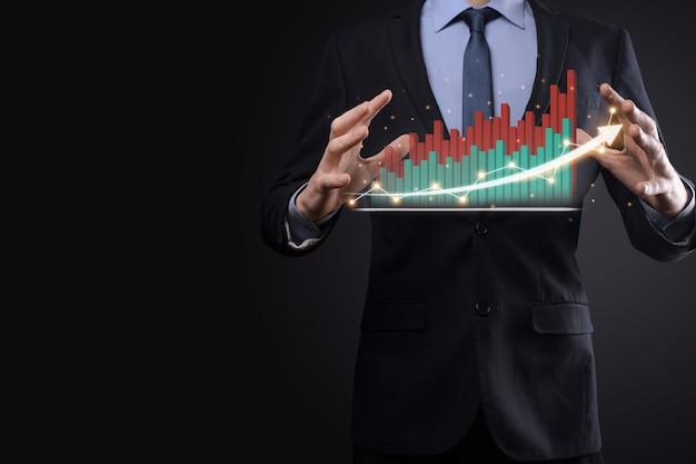Zakenman op een zwarte achtergrond persen, drukt een vinger op een positieve groei pijl. grafieken van indicatoren. bedrijfsontwikkeling en financiënconcept.