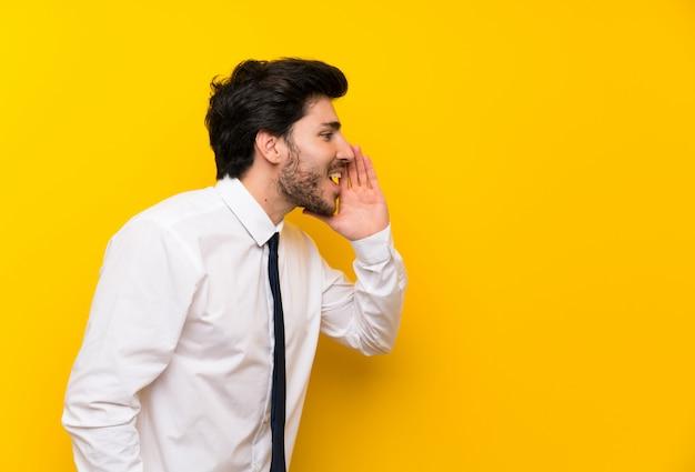 Zakenman op geïsoleerde gele achtergrond die met wijd open mond schreeuwen