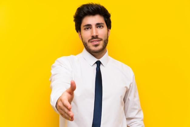 Zakenman op geïsoleerde gele achtergrond handshaking na goede deal