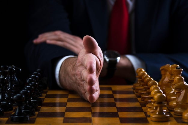 Zakenman op het schaakbord, hand scheidt witte en zwarte stukken