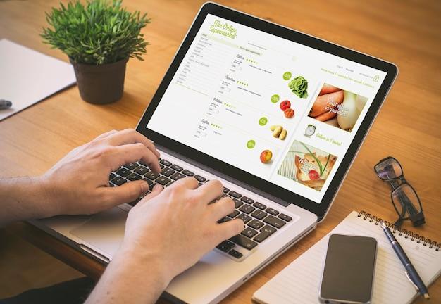 Zakenman op het werk. close-up bovenaanzicht van man online shooping op laptop zittend aan het houten bureau. reinig het scherm.