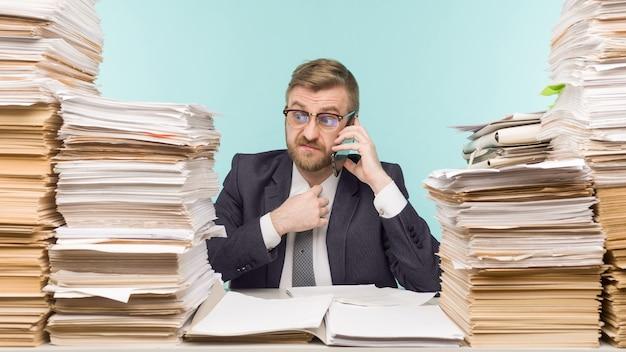 Zakenman op kantoor en stapels papierwerk, schold aan de telefoon voor slecht gedaan werk - imago