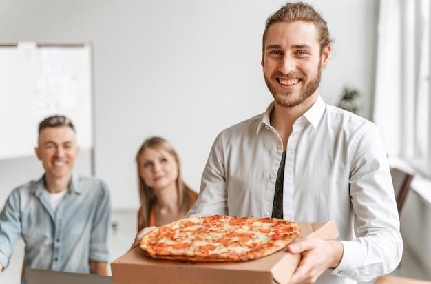 Zakenman op kantoor met pizza