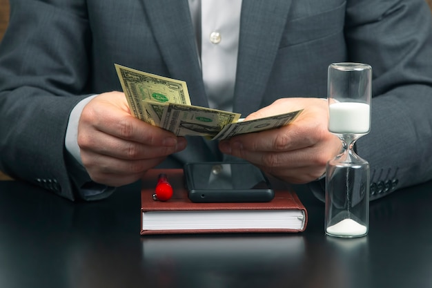 Zakenman op kantoor telt geld op een achtergrond van zonnewijzers. zaken en beloning.