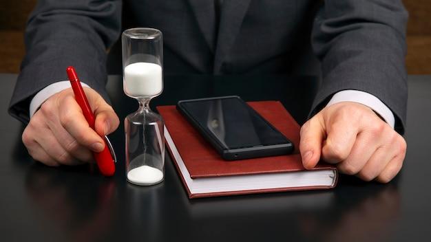 Zakenman op kantoor werkt met een mobiele telefoon op een zandloper