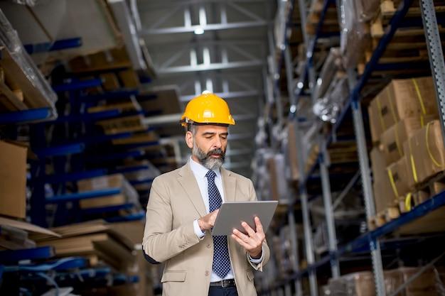 Zakenman op middelbare leeftijd met digitale tablet in fabriek