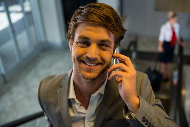 Zakenman op roltrap praten op mobiele telefoon