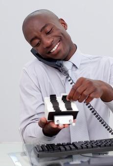 Zakenman op telefoon en kijken naar een indexhouder