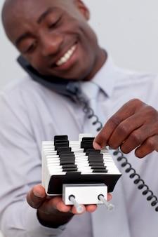Zakenman op telefoon en zoeken naar een indexhouder