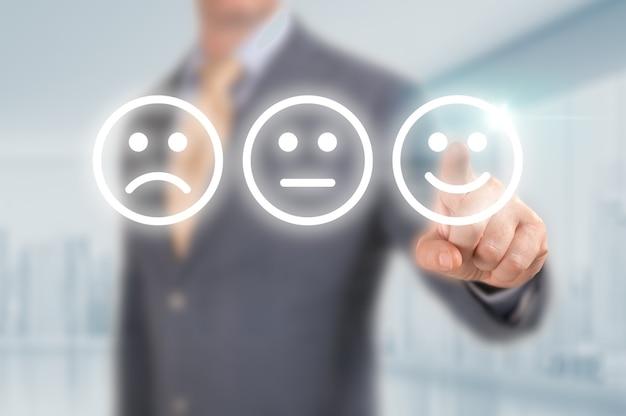 Zakenman op uitstekende smiley face rating icoon te drukken over lichtblauwe achtergrond