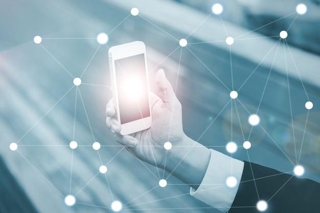 Zakenman op wazige achtergrond met behulp van digitale data-netwerk met mobiele telefoon