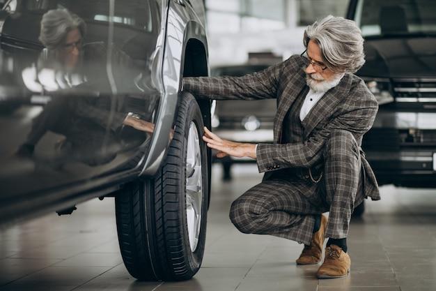 Zakenman op zoek naar een auto in een autosalon