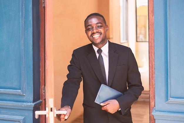 Zakenman opende de deur met een glimlach en wees vriendelijk