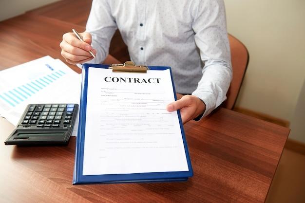 Zakenman overhandigt een contract met een balpen in de hand