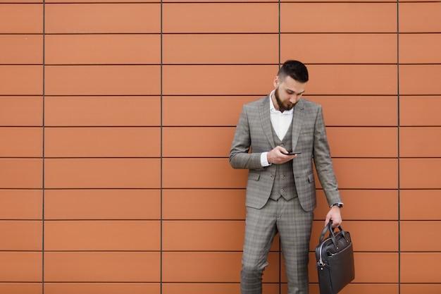 Zakenman pak dragen en met behulp van moderne smartphone in de buurt van kantoor in de vroege ochtend, succesvolle werkgever om een deal te sluiten terwijl hij in de buurt van wolkenkrabber staat