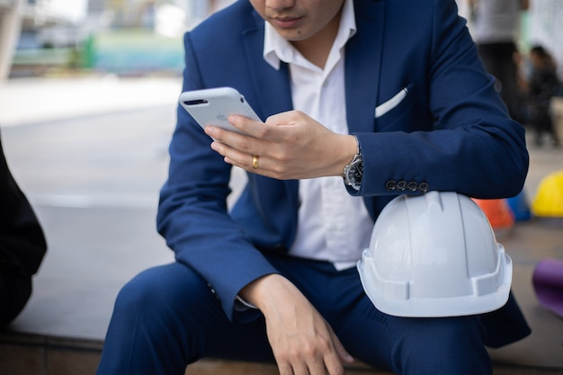 Zakenman passeert de tijd met behulp van mobiele slimme telefoon buiten.