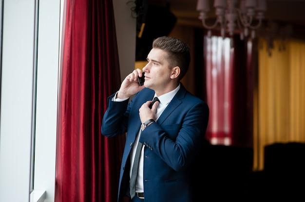 Zakenman past zijn das en praten aan de telefoon