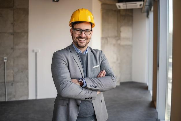 Zakenman permanent in gebouw in bouwproces met gekruiste armen