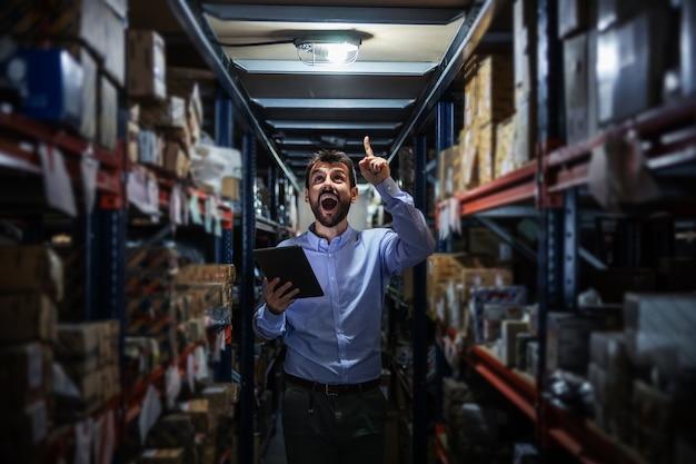 Zakenman permanent in magazijn vol met goederen voor levering. hij heeft een geweldig idee.