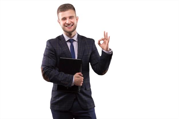 Zakenman permanent in pak met laptop in zijn handen en teken van ok . tonen