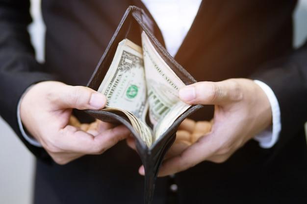 Zakenman persoon die een portemonnee in de handen van een man houdt, neemt geld uit de zak.