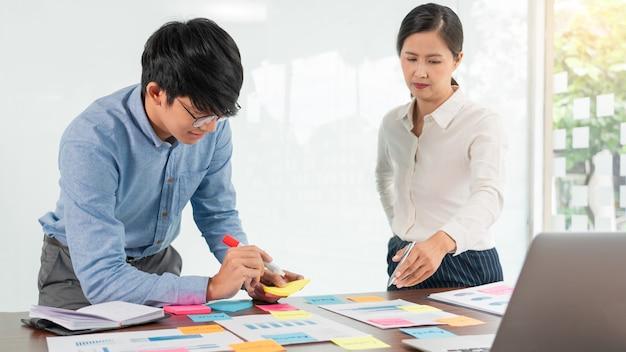 Zakenman plakt kleurrijke notities om te brainstormen op de tafel die aan een nieuw project werkt