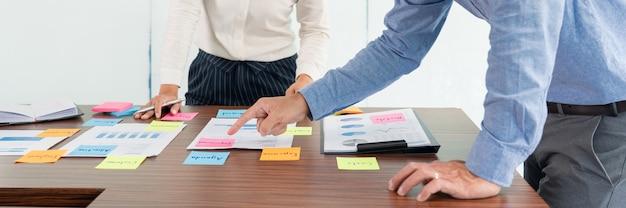 Zakenman plakt kleurrijke notities om te brainstormen op de tafel terwijl hij aan een nieuw project werkt om het idee te delen en na te denken over het plannen van een nieuwe zaak.