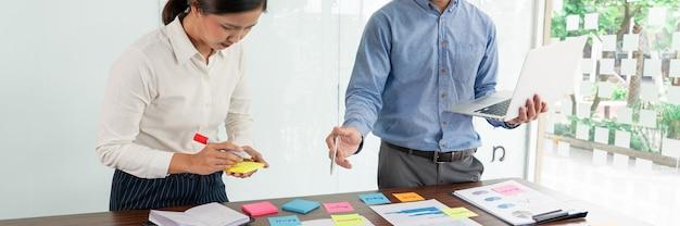 Zakenman plakt kleurrijke notities om te brainstormen op de tafel terwijl hij aan een nieuw project werkt om het idee te delen om na te denken over het plannen van een nieuwe zaak.