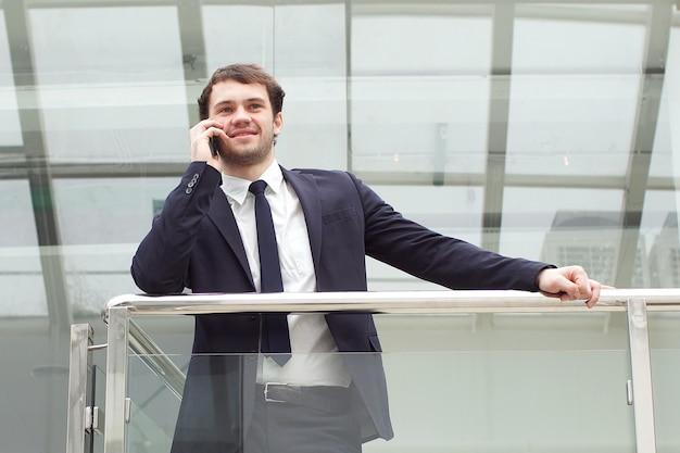 Zakenman portret. gelukkig zakenman staan, glimlachen, camera kijken.