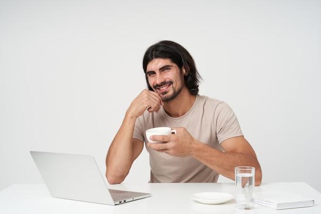 Zakenman, positieve man met zwart haar en baard. kantoor concept. op het werk zitten en koffiepauze houden. kin aanraken en glimlachen. geïsoleerd over witte muur