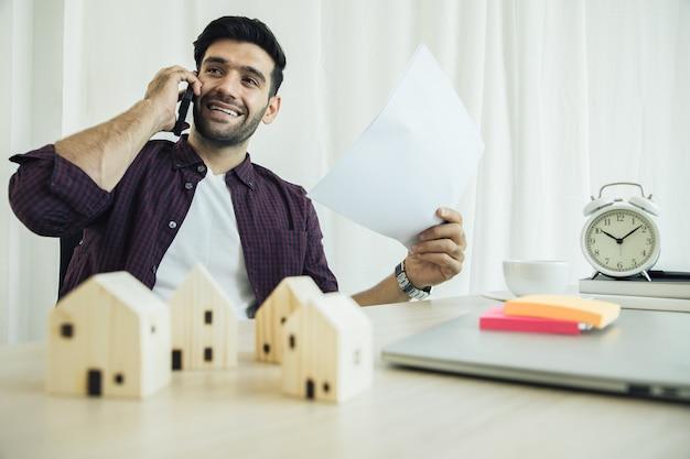 Zakenman praten aan de telefoon met vier houten huizen, een laptop en een wekker op zijn bureau