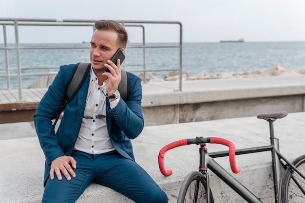 Zakenman praten aan de telefoon naast zijn fiets