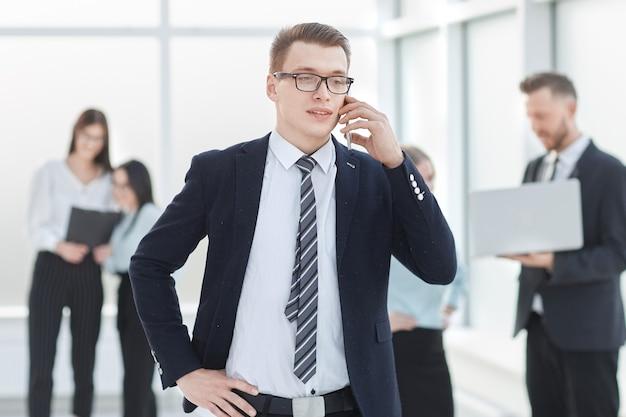 Zakenman praten over een smartphone, staande in de lobby van het zakencentrum