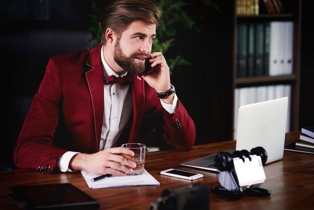 Zakenman praten via de telefoon in zijn kantoor
