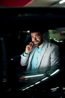 Zakenman praten zittend in een auto bij garage werken.
