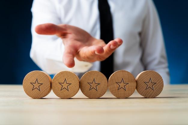 Zakenman presenteert vijf houten gesneden cirkels met sterren op hen in conceptueel beeld van luxe.