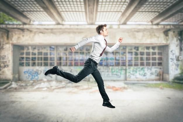 Zakenman rennen en springen, stedelijke achtergrond.