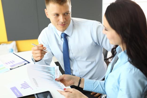 Zakenman schema's uit te leggen aan vrouw stagiair in kantoor