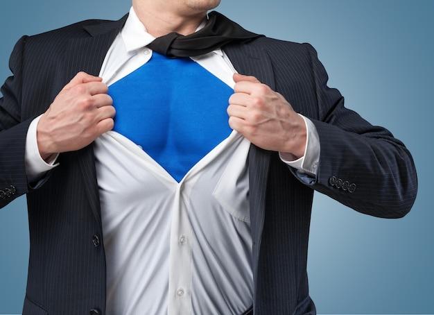 Zakenman scheurt hemd op zichzelf om te laten zien dat hij superman is geïsoleerd op de achtergrond