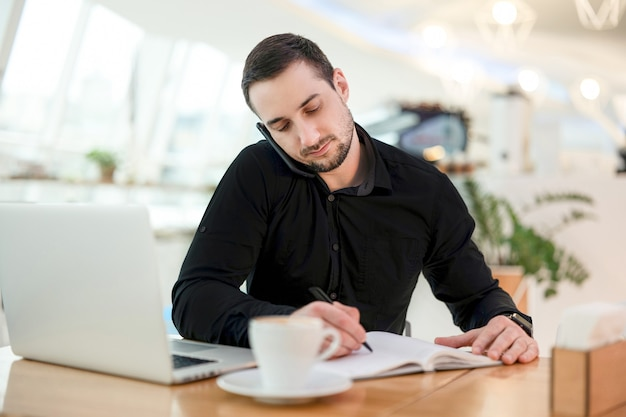 Zakenman schrijft datum van ontmoeting met klant in zijn planner. jonge man in zwart shirt werkt vanuit koffiehuis, drinkt cappuccino en gebruikt zijn moderne laptop.