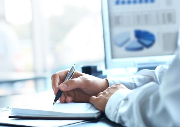 Zakenman schrijft in een notitieblok terwijl hij aan een bureau zit.
