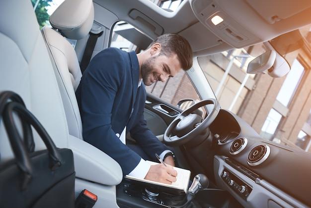 Zakenman schrijft notities in de auto en maakt zich klaar voor een vergadering
