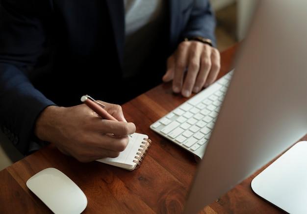 Zakenman schrijven in een notitieblok op zijn bureau