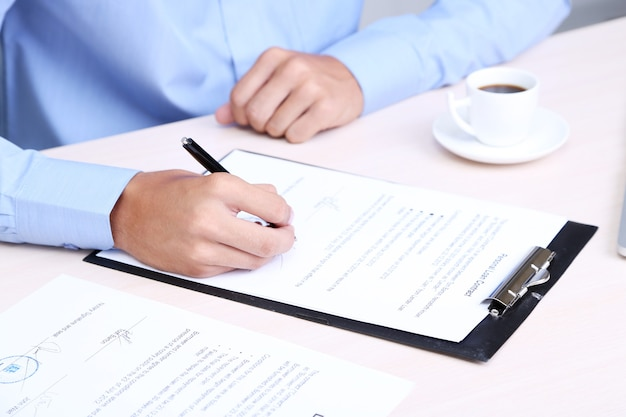 Zakenman schrijven op document in kantoor close-up