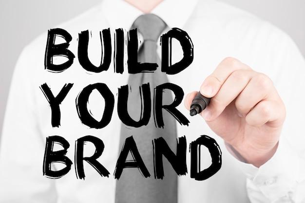 Zakenman schrijven woord bouwen uw merk met marker, bedrijfsconcept