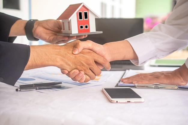 Zakenman schud de hand overeenkomst voor het succes van het huis van het verkoopcontract