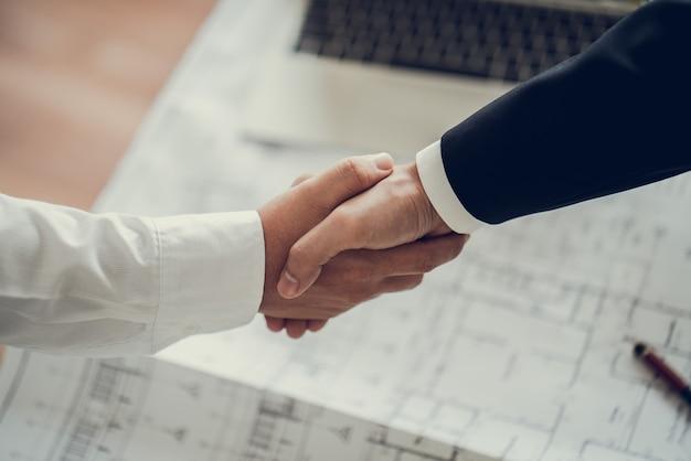 Zakenman schudden elkaar de hand, gaan akkoord met de verkoop van grote hoeveelheden die het doel van de marketingplannen van het bedrijf voltooien