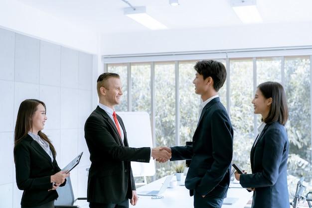 Zakenman schudden handen eens deal veel grote verkopen die doel van marketingplannen van het bedrijf voltooien