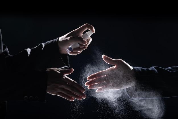 Zakenman schudt handen met pakvrouw en sproeit ontsmettingsalcohol 70% om coronavirus of covid-19 te doden voor het schudden, nieuw normaal business lifestyle-concept, donkere lage blootstelling